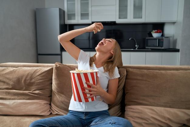 Женщина сидит на диване и ест попкорн