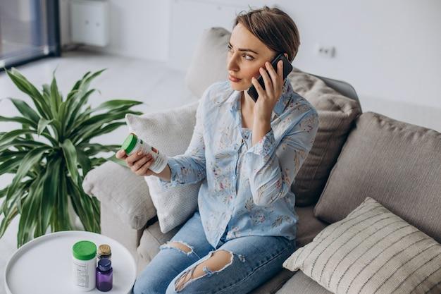 Женщина, сидящая на диване и держащая таблетки витаминов
