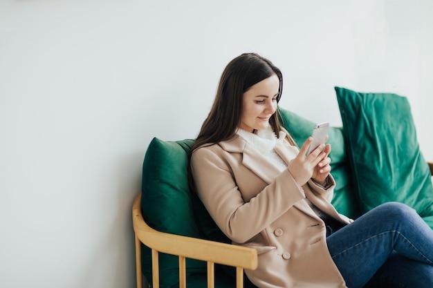 カフェのソファに座ってスマートフォンを使用している女性