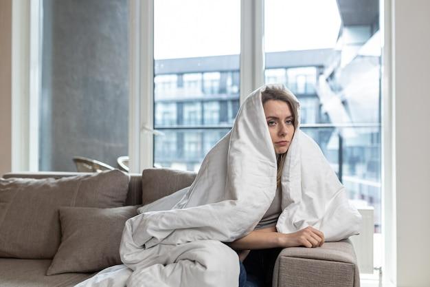 Женщина сидит на диване у себя дома депрессивная девушка с трудом справляется со стрессом