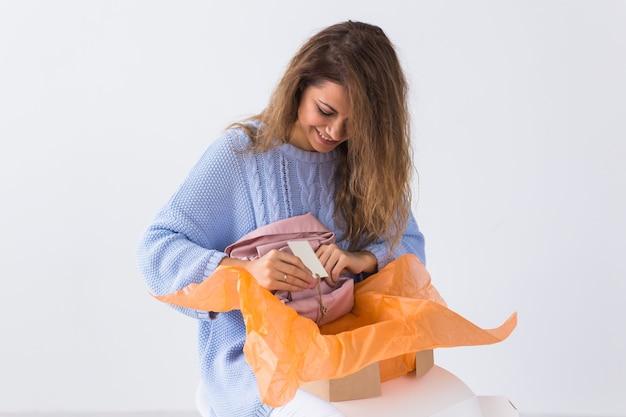 自宅のソファに座っている女性がオンライン衣料品の購入を開く