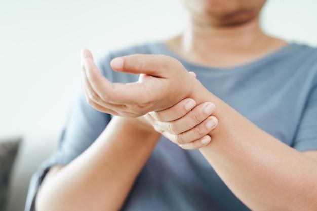 소파에 앉아 있는 여성은 손목 부상을 입고 고통을 느끼고 있습니다. 건강 관리 및 의료 개념