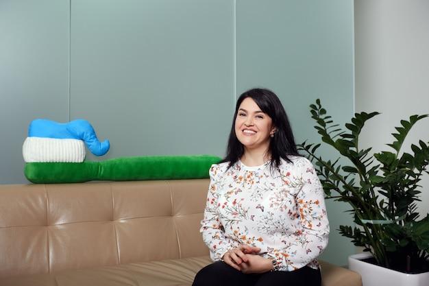 Женщина сидит на диване в приемной клиники, улыбаясь большой зубной щетке