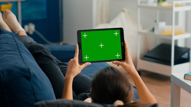 녹색 화면 크로마 키 디스플레이가 있는 태블릿 컴퓨터로 영화를 보고 있는 거실 소파에 앉아 있는 여성. 소셜 네트워크 탐색을 위해 격리된 터치스크린 장치를 사용하는 프리랜서