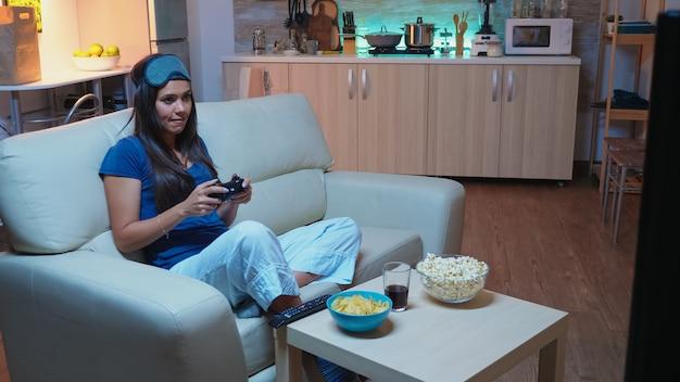 밤 늦게 소파에 앉아 비디오 게임을 하는 여성은 이마에 아이 마스크를 쓰고 있었습니다. 컨트롤러 조이스틱 키패드 플레이 스테이션 게임을 사용하고 전자 게임에서 승리하는 것을 즐기는 열성적인 결정된 게이머