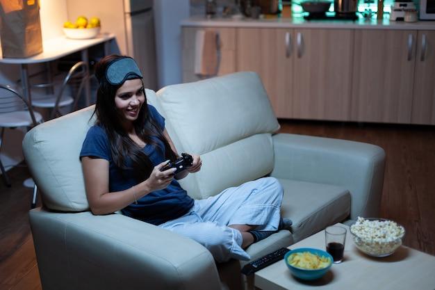 소파에 앉아 비디오 게임을 하고 웃고 있는 여성이 저녁을 즐기며 편안하게 웃고 있습니다. 컨트롤러 조이스틱 키패드 플레이 스테이션 게임을 사용하고 전자 게임에서 승리하는 것을 즐기는 열성적인 결정된 게이머