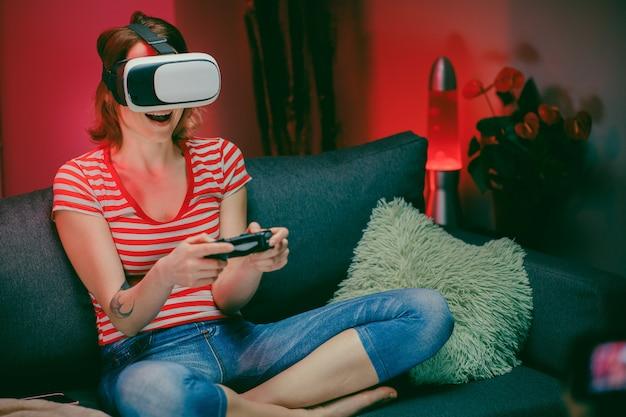 ビデオゲームをプレイするvrゴーグルを使用してソファーに座っている女性。ビデオゲームを楽しむリラックスした女性