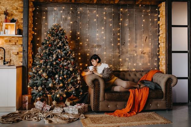 自宅のクリスマスツリーの横にコーヒーやお茶と一緒にソファに座っている女性