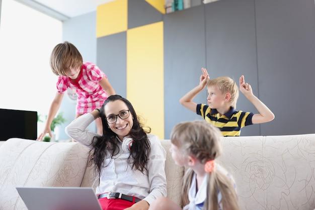 집에서 작은 아이들 옆에 노트북과 함께 소파에 앉아있는 여자