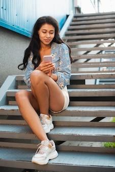 階段の上に座って、彼女の電話を見ている女性