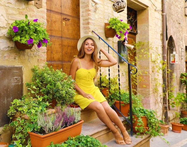 花と植物の間の家の階段に座っている女性
