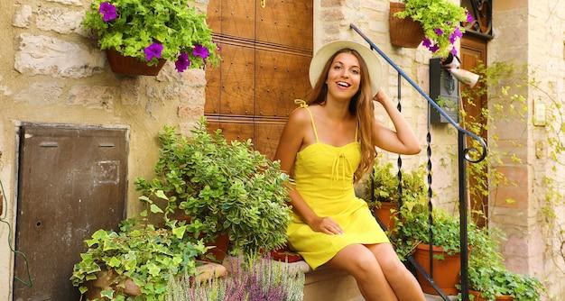 イタリア、アッシジのカラフルな花と植物の間にある階段の家に座っている女性
