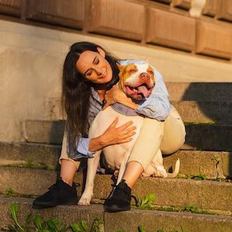 Женщина сидит на каменной лестнице и обнимается со счастливым американским питбультерьером