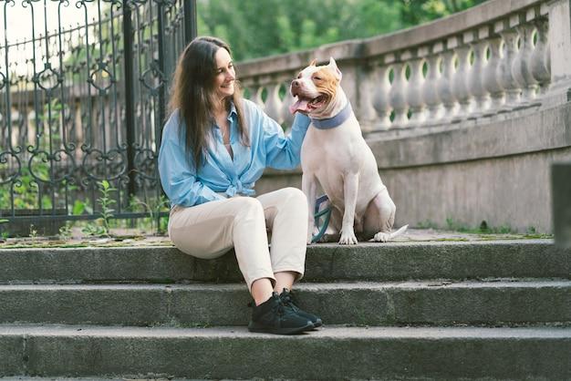 Женщина сидит на каменной лестнице и поглаживает счастливую собаку американского питбультерьера, глядя на владельца