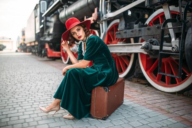 Женщина, сидящая на чемодане против паровоза