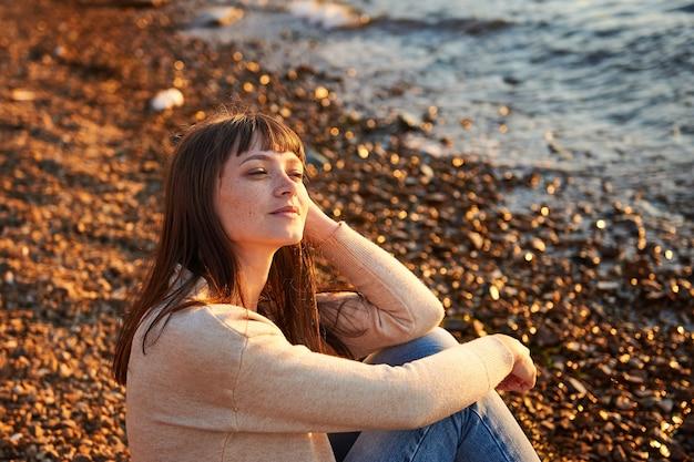 Женщина, сидящая на пляже на закате