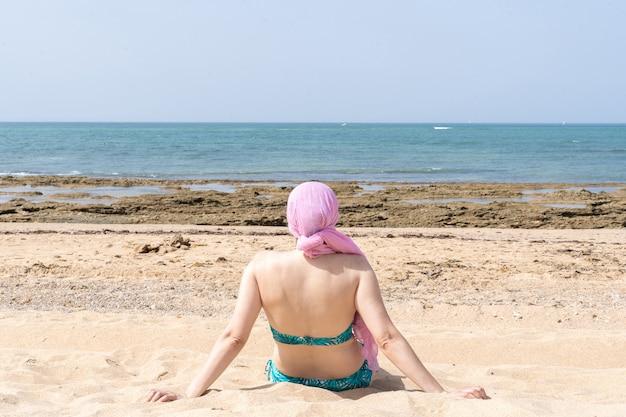 ピンクのスカーフを頭に抱えて海を見ているビーチに座っている女性、ガン。