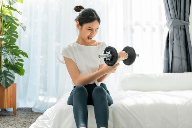 ベッドに座って、重すぎるダンベルを持ち上げて運動をしている女性。
