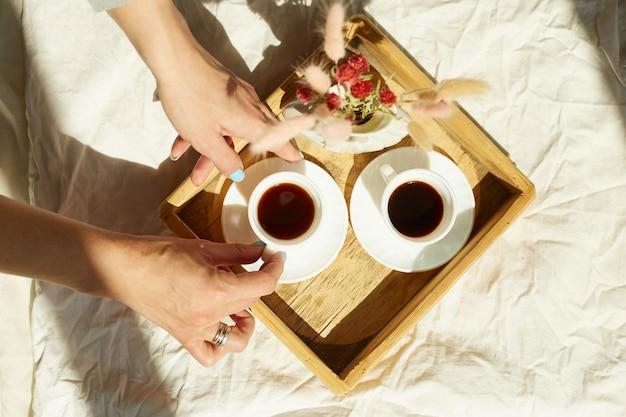 여자는 침대에 앉아 아침 햇살을 받으면서 커피를 마시고, 침대에서 아침을 먹습니다.