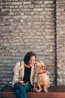 Женщина сидит на скамейке и с помощью телефона, когда собака лижет ее лицо