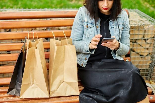 Женщина сидит на скамейке в парке с бумажными хозяйственными сумками после покупок