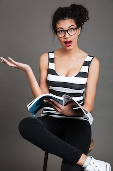 Женщина сидит на стуле с раскрытым журналом