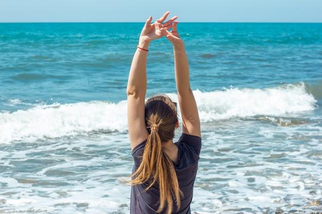 Женщина сидит на берегу, поднимая руки вверх