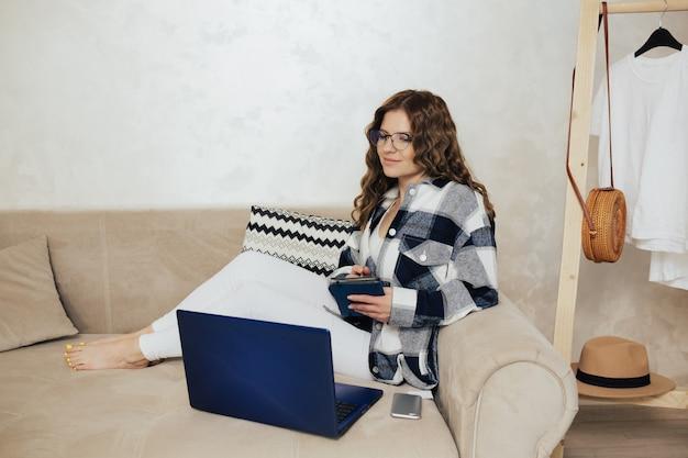 여자는 소파에 앉아 그녀의 노트북을 보면서 노트북에 메모를