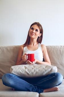コーヒーを飲みながらソファに座っている女性