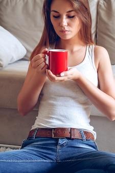 Женщина, сидящая на диване, пьет кофе