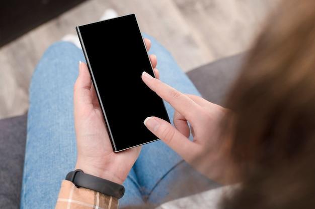 ソファに座っている女性はコピースペース付きの携帯電話を使用しています