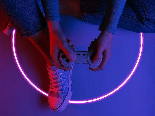 Женщина сидит на полу и держит геймпад. футуристическая эстетика светящегося круга 80-х synth wave и retrowave