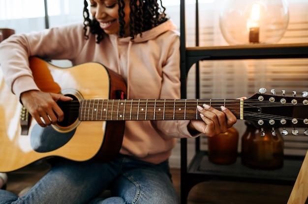 床に座って自宅でギターを弾く女性、接写。楽器を持つかわいい女性が部屋でくつろぎ、女性の音楽愛好家が休む