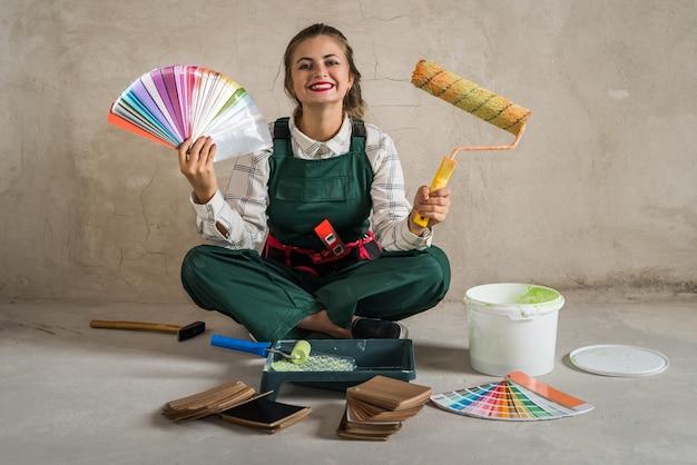 Женщина сидит на полу и позирует с инструментами для рисования