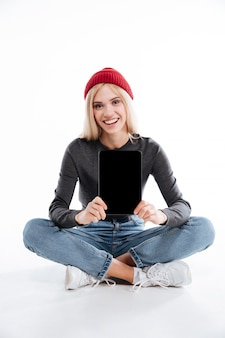 여자는 바닥에 앉아서 빈 화면 태블릿을 보여주는