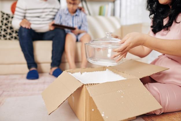 Женщина сидит на полу дома и достает новую стеклянную миску из картонной коробки, которую она получила