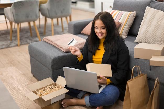 Женщина сидит на полу при совершении новой покупки