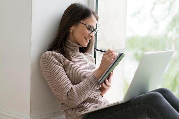 여자가 그녀의 노트북에서 일하는 바닥에 앉아
