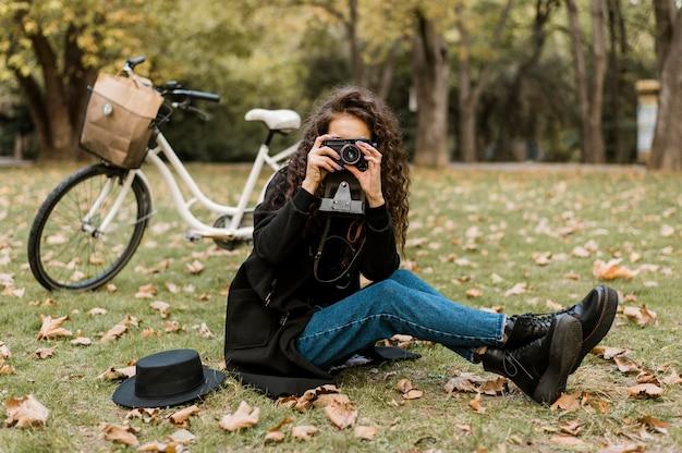 草の上に座って写真を撮る女性