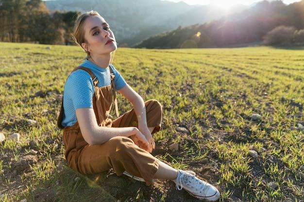 日光の下で地面に座っている女性