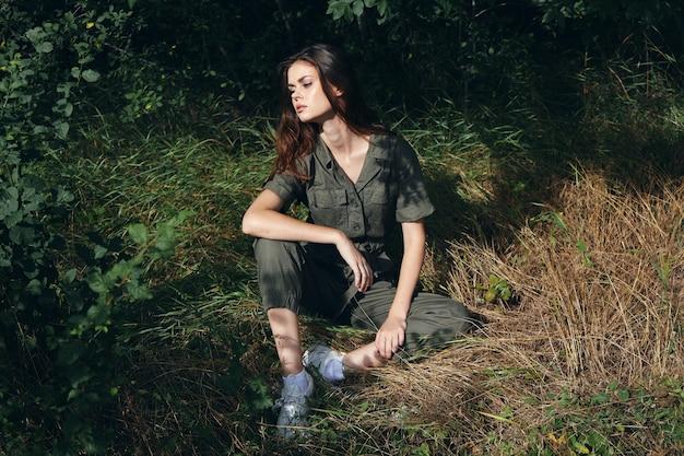 숲 녹색에서 바닥에 앉아있는 여자는 신선한 공기 휴식을 떠난다