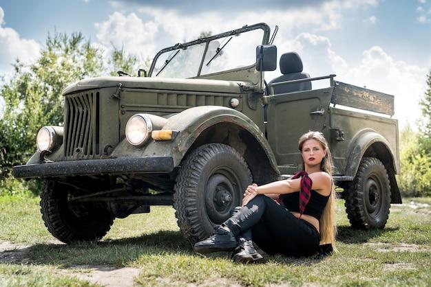 군사 차 근처 바닥에 앉아있는 여자