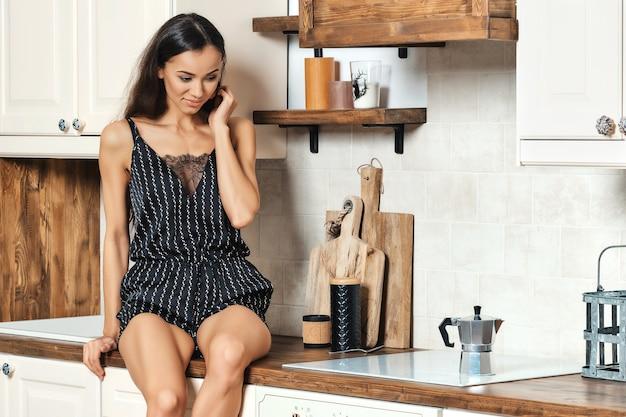 Женщина, сидящая на кухонном столе