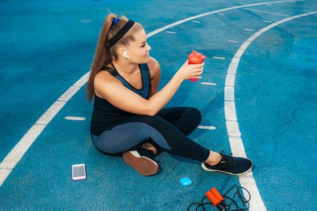 水のボトルと遊び場に座っている女性