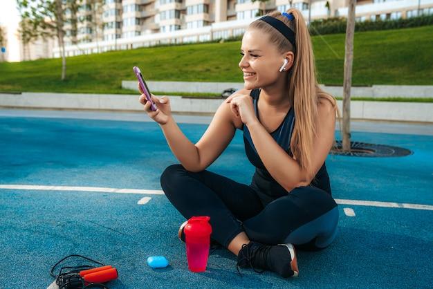 Женщина сидит на детской площадке с телефоном в руках