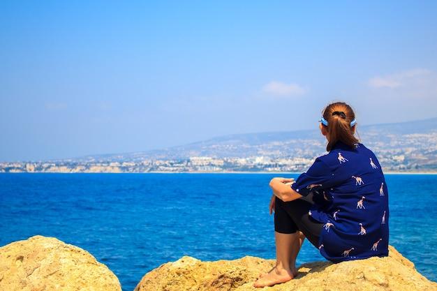 岩の上に座って、海の背景を見ている女性。 Premium写真