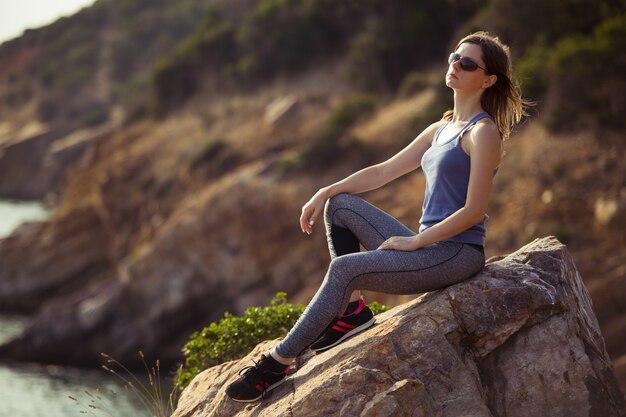 Женщина сидит на скале рядом с приморским альпинистом на вершине горы