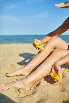 砂浜に座って、肌の脚に日焼け止めを塗って、暑い日に日焼け止めを日焼けさせる女性