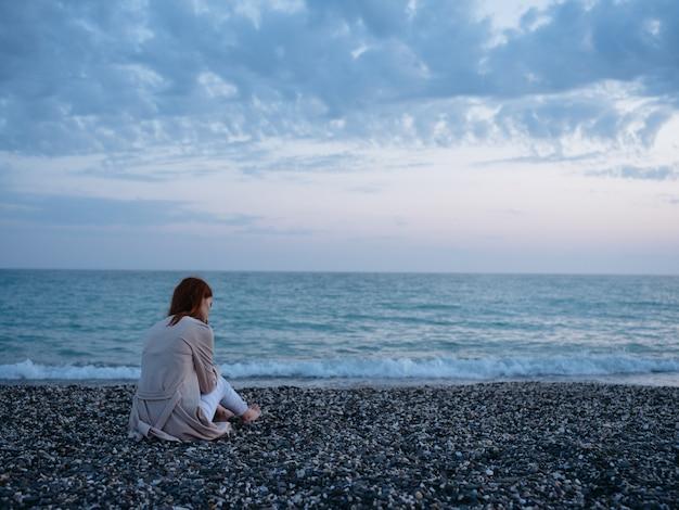 해변과 구름 푸른 하늘 다시보기에 앉아 여자.