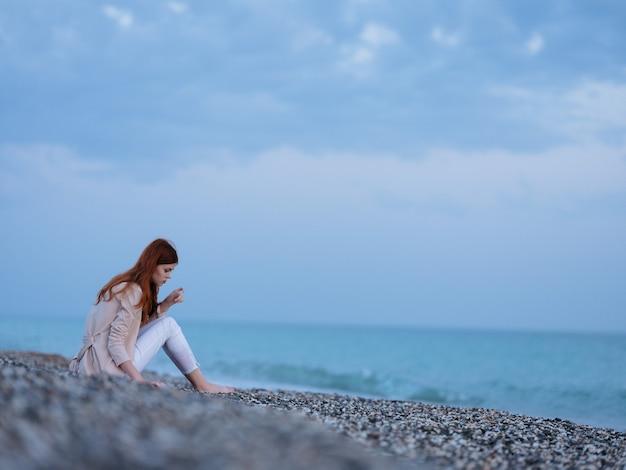 海岸のビーチに座っている女性海の風景新鮮な空気